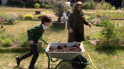 A school boy pushes a wheelbarrow full of soil.