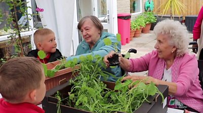 Schoolchildren and the care home residents gardening