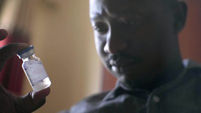 Alan Kasujja holding a bottle of medicine