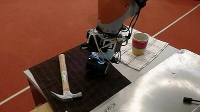 A robotic arm on a table, on the left-hand side is a hammer, on the right-hand side is a mug on top of a tea towel