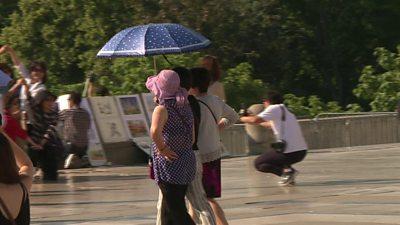 Three women shelter under an umbrella during a heatwave in Paris