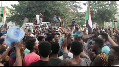 People wave flags and cheer in the streets