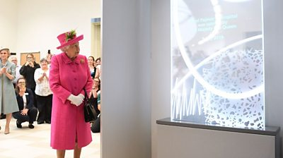 The Queen looks at a plaque