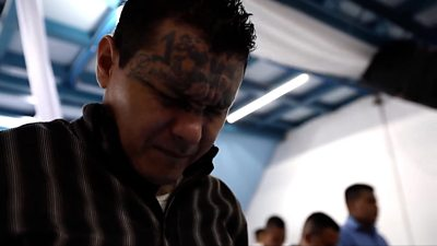 A man with face tattoos praying