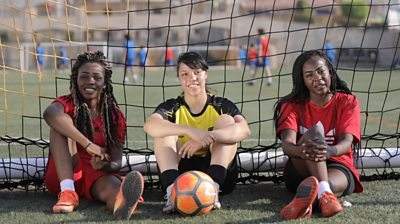 Three Egyptian women footballers sitting in a goal with a ball at their feet