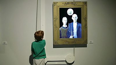 A child uses an interactive art exhibit at a museum