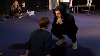 An actor crouching in front of another
