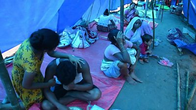 Displaced residents sit in a tent crying
