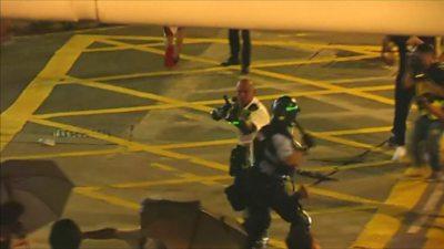 Policeman points gun at protesters in Hong Kong