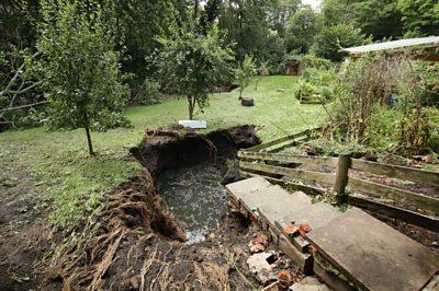A sink hole in a garden after heavy rain.