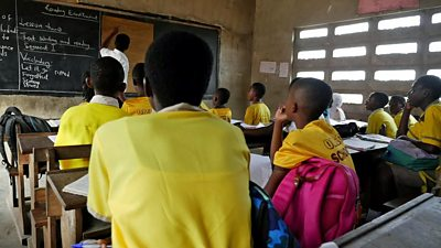 Pupils and a teacher in a schoolroom in Ghana