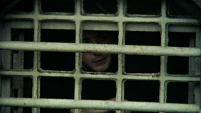 A young man looks through the bars of a prison