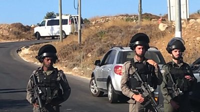 Israeli troops stand guard where the body of a 19-year-old soldier was found in the West Bank