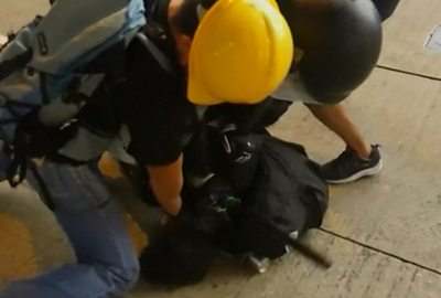 Hong Kong police arrest a protester with the help of a suspected undercover officer