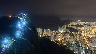 People light up mobile phones on Lion Rock above Hong Kong as part of a human chain of protest