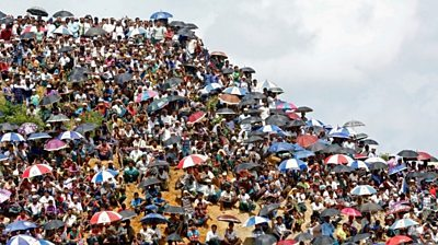 Hundreds of people can be seen crowding a hilltop