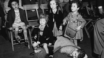 Children with suitcases waiting to be collected
