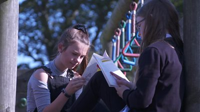 Two girls reading a book in the park