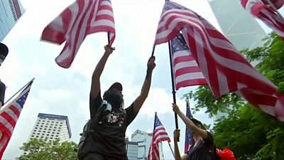 A man waves two US flags - one in each hand - in this frame
