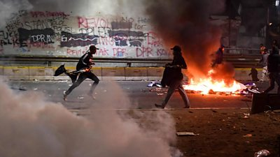 Protesters, tear gas and burning debris in Jakarta