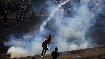 Demonstrator throws a tear gas canister in Baghdad