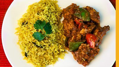 A plate of yellow pilau rice on the left and chicken curry on the right on a white plate.