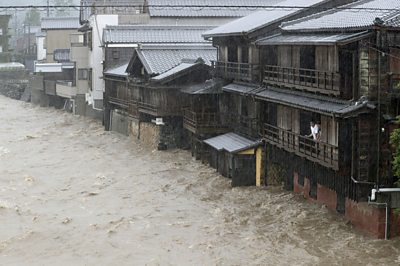 A man on a balcony watching the Isuzu river flood his street in Ise, central Japan