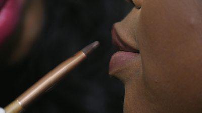 A makeup artist applies lip colour to a woman