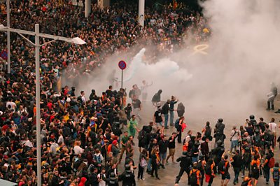Huge crowds of protesters clash with police officers at Barcelona airport