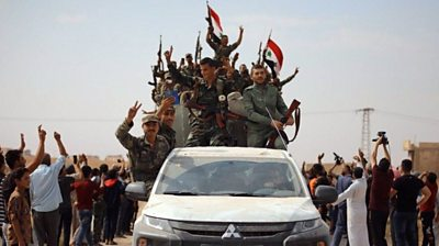 Syrian government forces wave national flags as they enter the northern town of Ain Issa