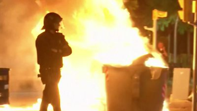 A riot policeman stands guard near a burning barricade in Barcelona