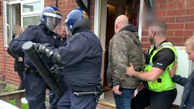 Police enter a house during a raid