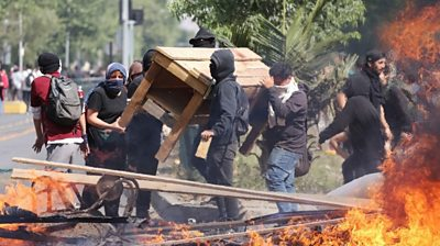People burn objects as demonstrations against the increase of metro fares take place, in Santiago