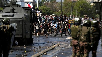 Demonstrators face off against the police during a protest in Santiago