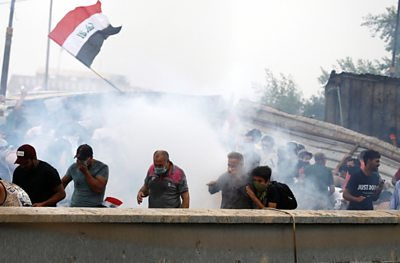 Demonstrators cover their faces from tear gas during a protest in Baghdad on 25 October 2019