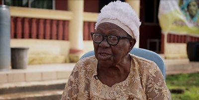 Jessie Onuigwe sits outside her home