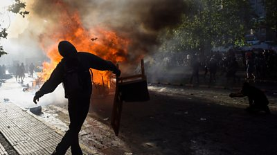 protester by a fire in Chile`