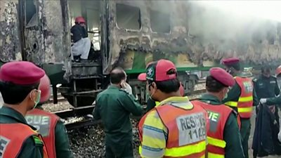 Emergency authorities survey the wreckage of a train fire in Pakistan