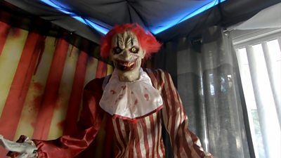 A scary clown hanging from the ceiling of a family home