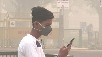 A young man wearing a breathing mask looks at his phone.
