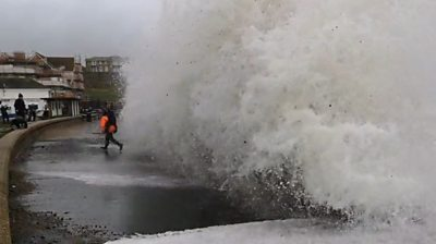 Man carrying child almost swept into sea