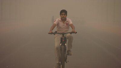 A boy rides a bike in Delhi, India