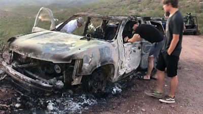 Relatives of the victims look over a burned-out car