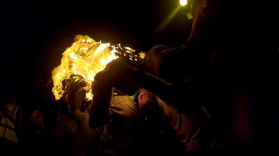 Flaming tar barrel carried through street