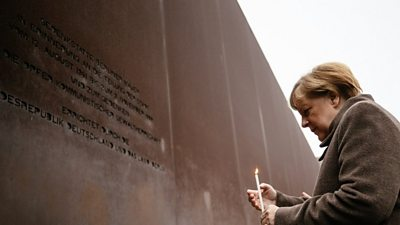 Mrs Merkel lit a candle at the memorial site