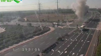 An explosion as a rocket hits a busy highway