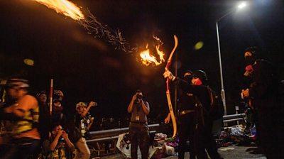 Protester shooting a flaming arrow