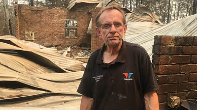 Warren Smith in front of his burnt-down home
