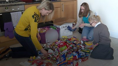 Danielle Shipman, Susan Lambe and a young girl sort materials for recycling