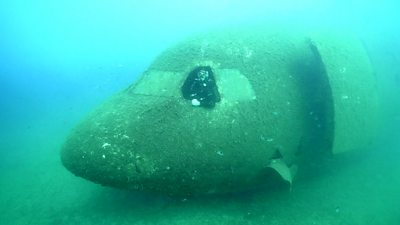A diver in the front of a plane under the sea
